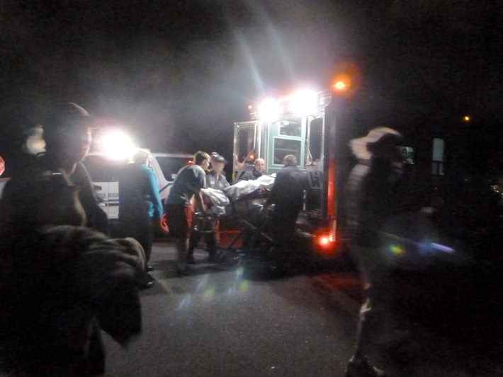 Night-time transfer of a patient to the EMTs of an ambulance crew, at a trail head parking area