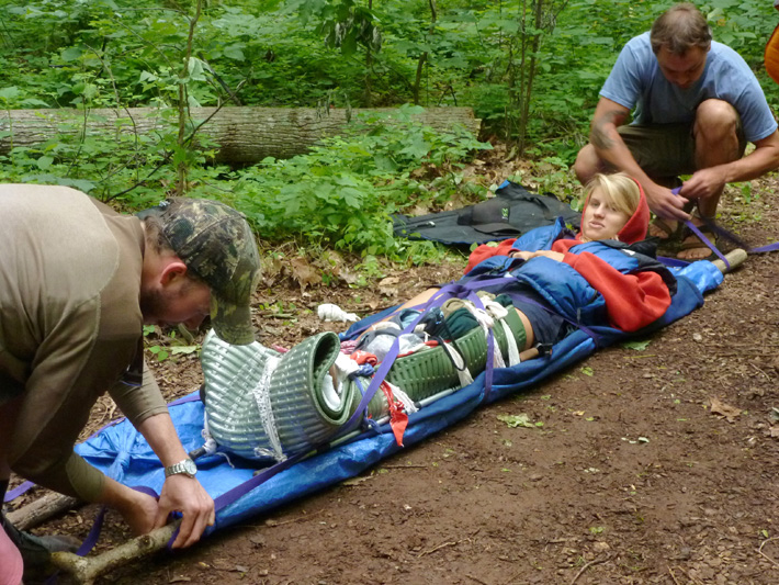Using a quickly-improvised litter made of sticks and a tarp to carry out a broken leg patient